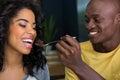 Loving man feeding dessert to woman in coffee shop Royalty Free Stock Photo