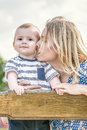 Loving mather kissing a baby boy on a wooden bench outdoor on nature at sunny summer say. Emotions of love Royalty Free Stock Photo