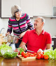 Loving mature couple cooking in kitchen with tomatoes at home Stock Image