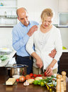 Loving mature couple cooking together in kitchen Stock Image