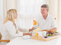Loving mature couple enjoying a healthy breakfast smiling at each other middle aged as they sit together table with tray of coffee Stock Images