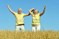 Loving mature couple in field jumping at summer Royalty Free Stock Photos