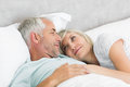 Loving mature couple lying in bed closeup of a men and women at the home Stock Photography