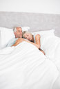 Loving mature man and woman lying in bed men women at the home Stock Images