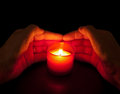 In loving memory - votive candle with hands Stock Photography