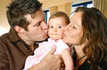 Loving mother and father kissing their baby girl Stock Image