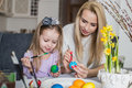 Loving mother and her daughter painting easter eggs cozy home atmosphere Stock Images
