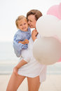 Loving mother and her small daughter share a tender happy moment as she holds the toddler in arms with a bunch of pink Royalty Free Stock Photo