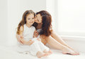 Loving mother kissing daughter at home in white room