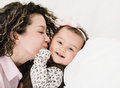 Loving mother kissing her baby isolated over white background Royalty Free Stock Photos
