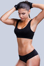 Loving my body beautiful young sporty woman with perfect posing against grey background Stock Photo
