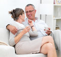 Loving  older couple sitting together on couch Royalty Free Stock Photography