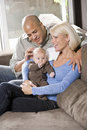 Loving parents with baby sitting on lap at home Royalty Free Stock Images