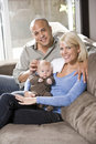 Loving parents with baby sitting on lap at home Stock Photos