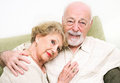 Loving senior couple at home relaxing on the couch Stock Photography