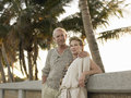 Loving senior couple leaning against wall on beach portrait of tropical Royalty Free Stock Photo