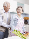 Loving senior couple men tying apron for his wife Royalty Free Stock Images