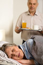 Loving senior husband serving breakfast to wife sleeping Stock Image