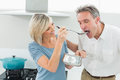 Loving woman feeding a man in kitchen women men the at home Royalty Free Stock Photos
