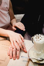 Loving woman hold man hand in her hands. Just married couple showing up wedding rings. Near Cup of latte coffee with chocolate on Royalty Free Stock Photo