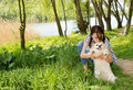Loving woman hugging her little dog cute and kissing the top of its head while the two enjoy a walk through lush green countryside Royalty Free Stock Photography