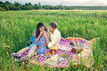 Loving young couple enjoying a date in the country sitting on red and white checked rug eating healthy picnic meal as Royalty Free Stock Photos