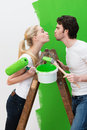 Loving young couple having fun while painting the wall a bright green standing on a wooden ladder facing each other Stock Photo