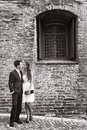 Loving young couple outside an old brick building black and white picture of stylish standing in intimate embrace on a cobbled Stock Image