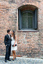 Loving young couple outside an old brick building stylish standing in intimate embrace on a cobbled street Stock Images