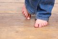 Low angle of little girl with bare feet front view on wooden floor Stock Images
