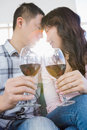 Low angle view of couple holding wineglasses while sitting at home Royalty Free Stock Photos