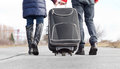 Low angle view of a couple pulling a suitcase walking side by side along an asphalt road in the countryside closeup their Royalty Free Stock Photos