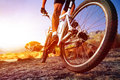 Low angle view of cyclist riding mountain bike on rocky trail at sunrise Royalty Free Stock Image