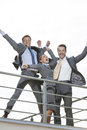 Low angle view of excited businesspeople with arms raised standing on terrace against clear sky Royalty Free Stock Photo