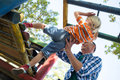 Low angle view of father assisting son in playing on jungle gym Royalty Free Stock Photo