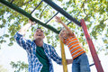 Low angle view of father and son playing on jungle gym Royalty Free Stock Photo
