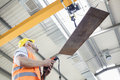 Low angle view of manual worker operating crane lifting sheet metal in industry Royalty Free Stock Photo