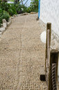 Low angle view of mediterranean pebble cobble path white wall an and garden Royalty Free Stock Photography