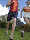 Low angle view of two young men running mountain in background Stock Photography
