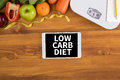 Low carb diet top view digital tablet on a wooden table fitness and weight loss concept dumbbells white scale towels fruit weight Stock Photos
