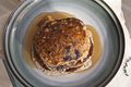 Low carb pancakes healthy blueberry stacked on a blue stoneware plate drizzled with maple syrup Royalty Free Stock Photography