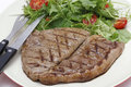 Low carb steak and salad with cutlery meal of grilled rump a home grown mix cherry tomatoes knife fork Stock Image
