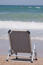 Low chair by the sea with waves Stock Photo