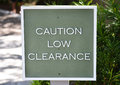 Low clearance sign a wooden green that reads caution Stock Images