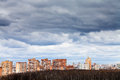 Low grey rainy clouds under city in spring Stock Photo