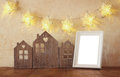 Low key image of vintage wooden house decor, blank frame on wooden table and stars garland. retro filtered. selective focus Royalty Free Stock Photo