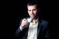 Low key portrait of a business man drinking coffee studio smiling Stock Photography