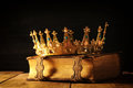 low key of queen/king crown on old book. vintage filtered. fantasy medieval period