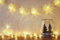 Low key and vintage filtered image of christmas trees in mason jar with garland warm lights and glitter overlay selective focus Stock Photography