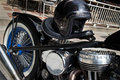 Low rider motorcycle with black helmet and chrome side angle view of a custom no brand engine fat rear wheel balances on top of Royalty Free Stock Photo